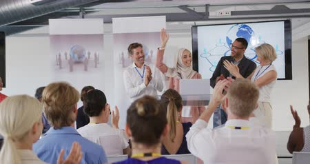 entre : Front view of a young Asian businesswoman wearing a hijab standing on a stage at a lectern between a diverse group of colleagues, raising her arm as her colleagues on stage and the seated audience applaud at a business conference. The backs of the seated  Vídeos