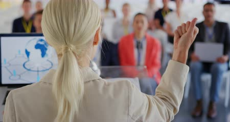 delegate : Back view close up of a young Caucasian businesswoman with blonde hair in a ponytail standing on a stage at a lectern with a laptop speaking and gesturing to the audience at a business conference. The seated audience are seen facing her in the background