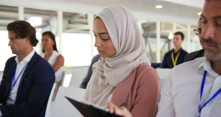 interessado : Side view close up of a young Asian businesswoman wearing a hijab sitting in the audience listening to a presentation at a business conference, a diverse group of other business people are seen sitting in the audience around her Vídeos