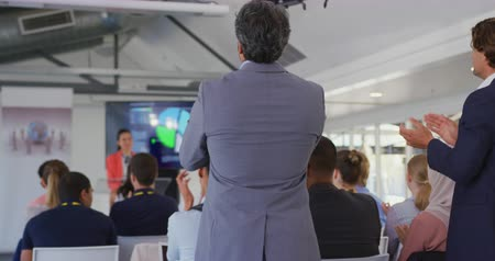 ringraziare : Rear view of the audience standing up from their seats and clapping at the end of a presentation at a business conference, the speaker and a display screen on stage visible in the background