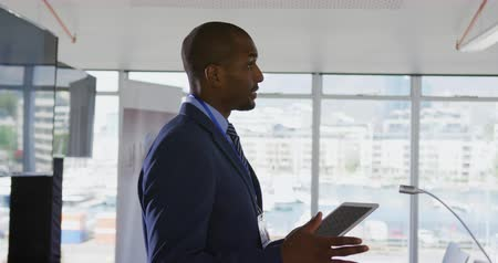 red tie : Side view close up of a young African American businessman wearing a suit and tie standing at a lectern holding a tablet and addressing the audience at a business conference