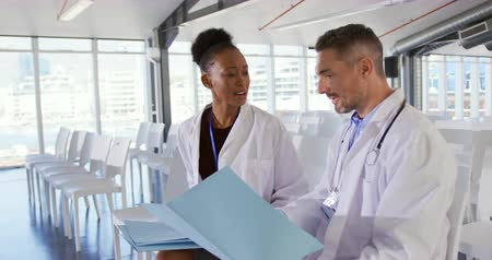 delegate : Close up side view of a middle aged Caucasian male doctor and a young mixed race female doctor sitting in an empty seminar room holding files and talking