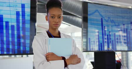 delegate : Portrait close up of a young mixed race female scientist wearing a white lab coat standing on the stage at a seminar in front of screens showing graphs and charts holding a document file and looking straight to camera
