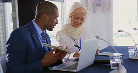delegeren : Side view close up of a young African American businessman and a young Asian businesswoman wearing a hijab sitting next to each other at a business conference talking and making notes