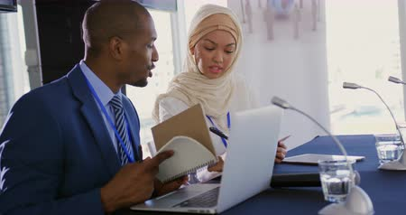 working together : Side view close up of a young African American businessman and a young Asian businesswoman wearing a hijab sitting next to each other at a business conference talking and making notes