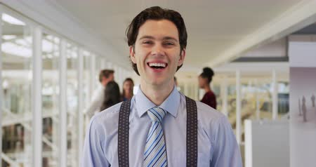 red tie : Portrait close up of a young Caucasian businessman looking to camera and smiling, standing in the foyer at a business conference, with other attendees talking in the background Stock Footage