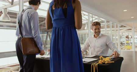 пять : Close up side view of a young Asian woman and a young Caucasian man sitting at a desk at the entrance to a business conference registering a young businesswomen and businessman and presenting name badges to them as they arrive
