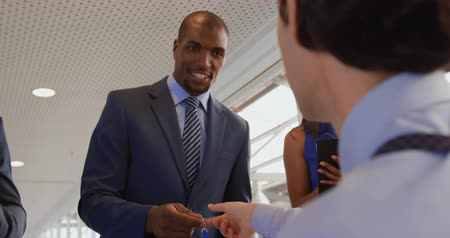 arriving : Over the shoulder view of a young Caucasian man sitting at a desk at the entrance to a business conference passing a name badge to a young African American businessman as he arrives Stock Footage