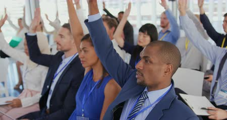 peça : Close up side view of a diverse audience at a business seminar all raising their hands to ask questions at the end of a presentation