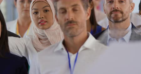 peça : Front view close up of a young Asian businesswoman wearing a hijab sitting in the audience at a business conference raising her hand to ask a question, a diverse group of other business people are seen sitting in the audience around her