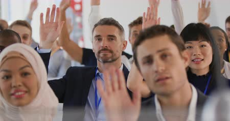 встреча : Close up front view of a diverse audience at a business seminar all raising their hands to ask questions at the end of a presentation