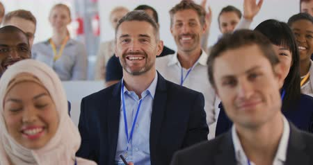 встреча : Close up front view of a diverse smiling audience at a business seminar all raising their hands to ask questions at the end of a presentation Стоковые видеозаписи