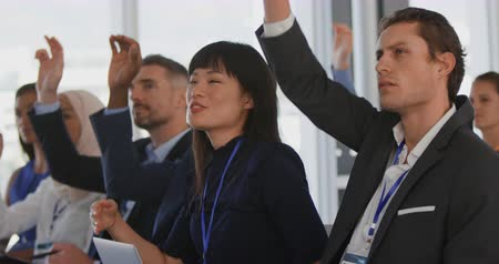 спрашивать : Close up side view of a diverse audience at a business seminar raising their hands to ask questions at the end of a presentation
