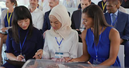 семинар : Front view close up of two young Asian businesswomen, one wearing a hijab, and a mixed race young businesswoman sitting in a row in the audience at a business seminar talking and looking at the notes they have been making, other members of the diverse aud