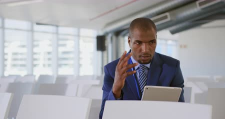 red tie : Front view close up of a young African American businessman wearing a suit and tie sitting holding a tablet, gesturing and practicing his speech before presenting at a business seminar Stock Footage