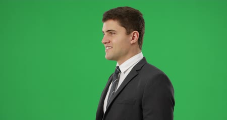 редактируемые : Side view close up of a young Caucasian man smiling and wearing a suit, shirt and tie on a green background