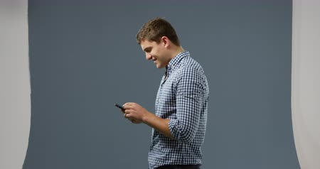 редактируемые : Side view of a young Caucasian man wearing a checked shirt, using a smartphone and smiling on a gey background