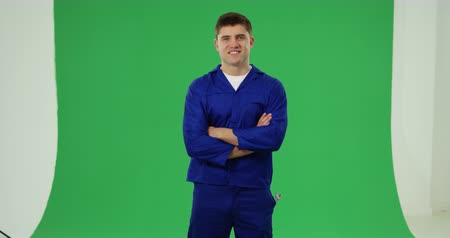 klussen : Front view of a young Caucasian handyman wearing blue overalls and cap smiling with crossed arms on a green background Stockvideo