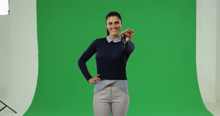 um : Front view of a young Caucasian woman holding keys and smiling to camera on a green background