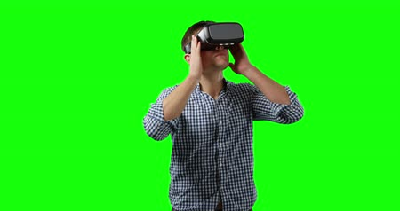 kruk : Front view of a young Caucasian man looking around, wearing a checked shirt and a VR headset, greenscreen