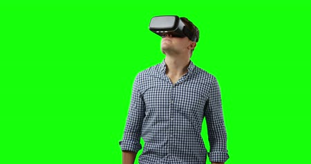 videogame screen : Front view of a young Caucasian man looking around, wearing a checked shirt and a VR headset, greenscreen