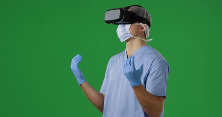 редактируемые : Side view close up of a young Caucasian male surgeon looking around and wearing scrubs, face mask, surgical gloves and VR headset on a green background