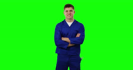 klussen : Front view of a young Caucasian handyman wearing blue overalls and cap smiling with crossed arms, greenscreen Stockvideo
