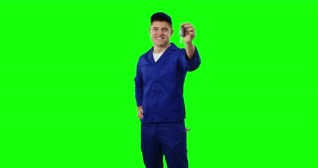 mülkiyet : Front view of a young Caucasian handyman wearing blue overalls and cap holding keys and smiling, greenscreen