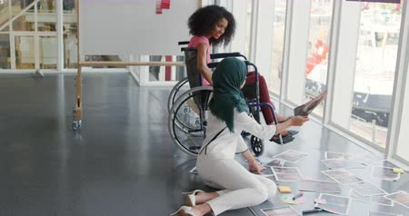 paraplegic : Side view of two young mixed race female business creatives working together and looking at pictures in a modern office, one woman wearing a hijab is sitting on the floor, the other woman is sitting in a wheelchair