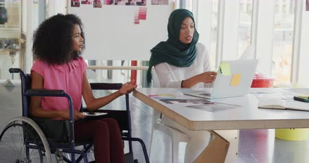 paraplegic : Front view of two young mixed race female business creatives working together and talking in a modern office, one is sitting in a wheelchair and holding a tablet computer, the other woman who is wearing a hijab is sitting at a desk using a laptop computer Stock Footage