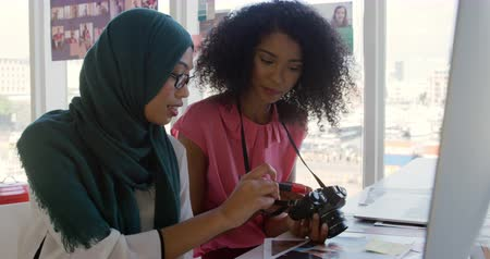 back side : Side view of two young mixed race female business creatives looking a images on the back of a digital camera in a modern office