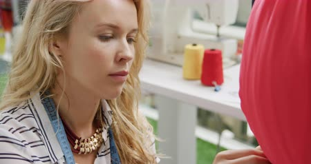 businesspeople : Side view close up of young Caucasian female fashion designer designing clothing on a mannequin in a fashion studio Stock Footage