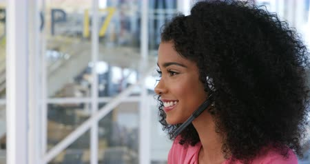 agência : Side view of a young mixed race female business creative working with headset on in a modern office Vídeos