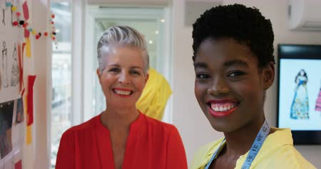 placa : Portrait of a middle aged Caucasian female fashion creative and a young African American female fashion creative smiling to camera in a modern office
