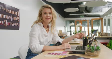 ügynökség : Portrait of a young Caucasian female business creative working in a modern office, using a laptop computer and smiling to camera