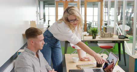 agência : Side view of a young Caucasian male and female business creatives working in a modern office, discussing and using a laptop computer