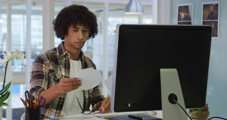 color swatch : Front view of a young mixed race male business creative working in a modern office, using a computer