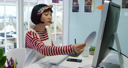 color swatch : Side view of a young mixed race female business creative working in a modern office, using a graphics tablet and colour wheel
