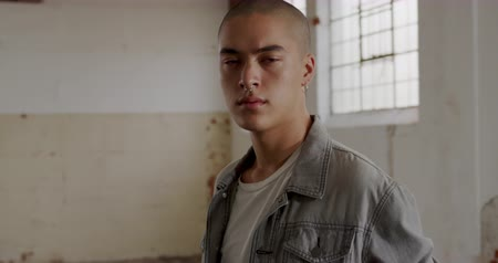 depilada : Portrait of a hip young mixed race man in an empty warehouse, looking to camera