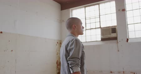 nem városi színhely : SIde view of a hip young mixed race man in an empty warehouse, looking around Stock mozgókép