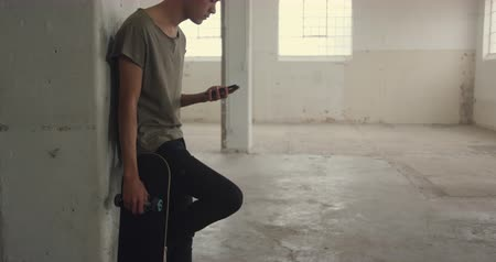 tárcsázás : Side view of a hip young mixed race man in an empty warehouse, leaning against a wall holding a skateboard and using a smartphone