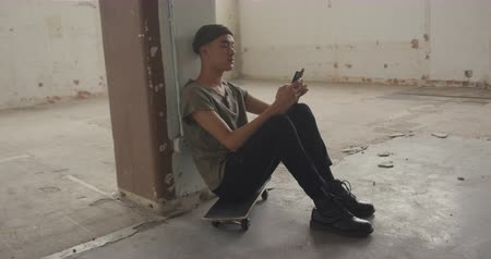 tárcsázás : Side view of a hip young mixed race man in an empty warehouse, sitting on a skateboard and using a smartphone