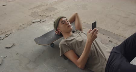 tárcsázás : Side view of a hip young mixed race man in an empty warehouse, lying on a skateboard and using a smartphone