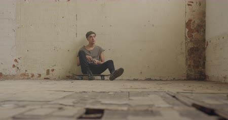 tárcsáz : Front view of a hip young mixed race man in an empty warehouse, sitting on a skateboard and using a smartphone Stock mozgókép