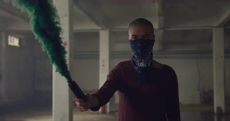 granada : Front view of a hip young mixed race man in an empty warehouse, holding a hand grenade with bandana covering his face
