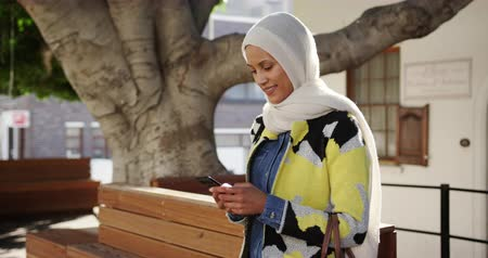 foulard : Side view of a young mixed race woman wearing a hijab standing in a city street, using a smartphone