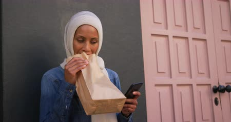 sarıcı : Front view of a young mixed race woman wearing a hijab standing in a city street, using a smartphone eating a sandwich Stok Video