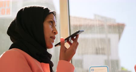 головной платок : Side view of a young mixed race woman wearing a hijab commuting sitting on a bus in a city, talking on the smartphone