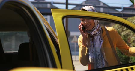 liga : Front view of a young mixed race woman wearing a hijab, talking on the smartphone and getting in a taxi in a city