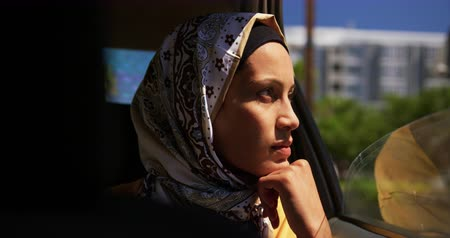eyes closed : Side view close up of a young mixed race woman wearing a hijab sitting in a taxi in a city, looking out of a window and closing her eyes